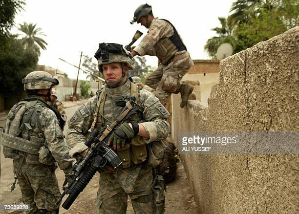 An Iraqi army soldier jumps across a compound wall as US soldiers secure the area during a search operation in Baghdad's alKarrada neighborhood 24...