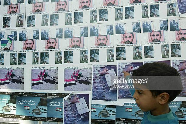 An Iraqi boy walks past posters showing AlQaeda frontman Abu Musab alZarqawi in Baghdad 18 December 2005 At least 10 Iraqis were killed as violence...