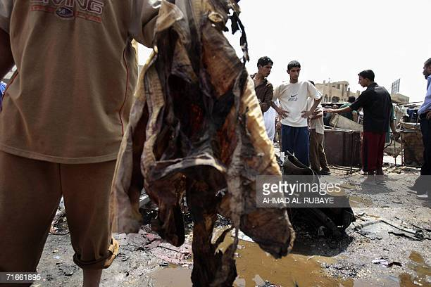 An Iraqi carries a blood soaked shirt at the site where a car bomb exploded in Baghdad's poor neighborhood of Sadr City 17 August 2006 Four Iraqis...