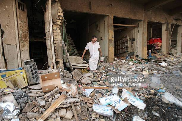 An Iraqi inspects destruction at the site of a car bomb explosion in Baghdad's Karrada neighborhood 27 July 2007 A powerful car bomb rocked central...