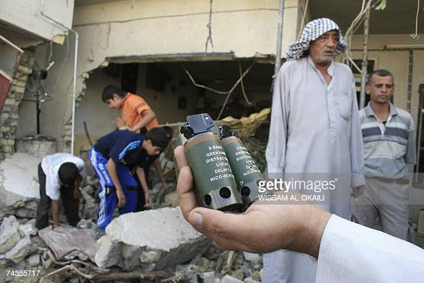 An Iraqi man shows photographers bang grenades found in the rubble of a damaged house raided by US soldiers in Baghdad's Sadr City 30 May 2007 Five...