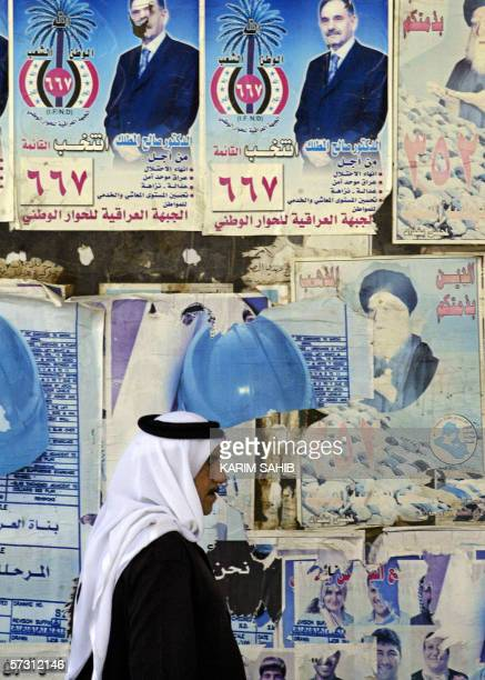 An Iraqi man walks past old Shiite and Sunni election posters still hanging along the streets of Baghdad 11 April 2006 Amid escalating sectarian...
