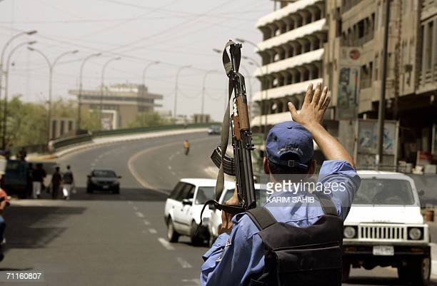 An Iraqi policeman stops cars few minutes before that start of curfew in central Baghdad 09 June 2006 after the wartorn capital was placed under...