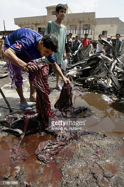 An Iraqi removes a blood soaked dress from the site where a car bomb exploded in Baghdad's poor neighborhood of Sadr City 17 August 2006 Four Iraqis...