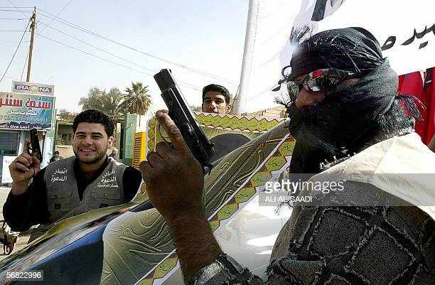 An Iraqi Shiite protester from alDawa party brandishe their guns as they take part in a demonstration 11 February 2006 in central Baghdad over the...