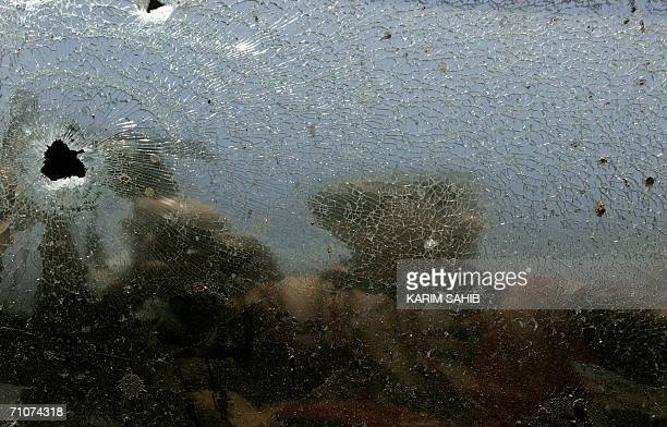 An Iraqi soldier is reflected on broken car shield glass at the site where a bomb exploded in kazemiya district north of Baghdad 29 May 2006 At least...