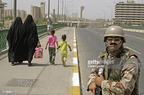 An Iraqi soldier secures a bridge few minutes before the start of a curfew in central Baghdad 09 June 2006 after the wartorn capital was placed under...