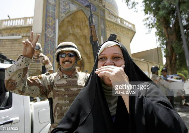 An Iraqi ululate in joy as an Iraqi soldier flashes the V sign minutes after hearing Iraqi Prime Minister Nuri alMaliki announcing 08 June 2006 the...