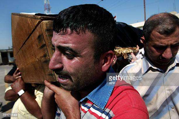 An Iraqi weeps as he caries the coffin of Lieutenant General Amer alHashemi during his funeral in Baghdad 09 October 2006 Unidentified gunmen...