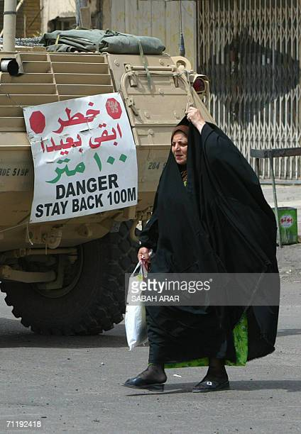 An Iraqi woman adjusts her abaya as she passes by a US army armored vehicle at the scene of a car bomb attack in Baghdad 08 May 2006 A roadside bomb...