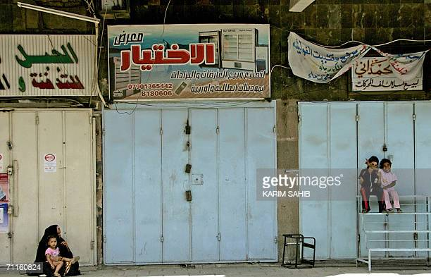 An Iraqi woman and her children sit in the shade of closed shopes in central Baghdad 09 June 2006 after the wartorn capital was placed under curfew...