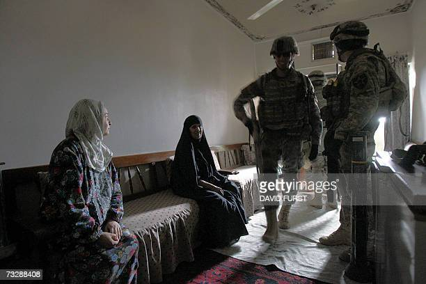 An Iraqi woman looks at US Army soldiers from Bravo Company 520 Infantry Regiment as they walk through her home in search of an overwatch position in...