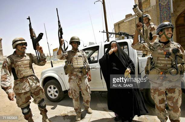 An Iraqi woman shares Iraqi soldiers their joy minutes after hearing Iraqi Prime Minister Nuri alMaliki announcing 08 June 2006 the death of alQaeda...