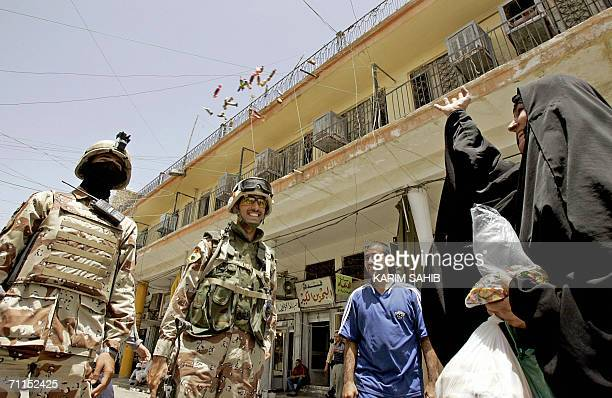 An Iraqi woman throws candies at an Iraqi soldier as she jubilates in Baghdad after hearing Iraqi Prime Minister Nuri alMaliki announcing 08 June...
