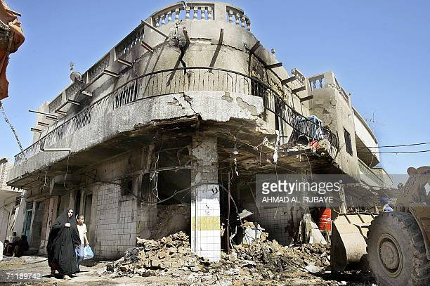 An Iraqi woman walks 13 June 2006 near a destroyed building at the site where a car bomb exploded in a Shiite market yesterday night in Baghdad At...