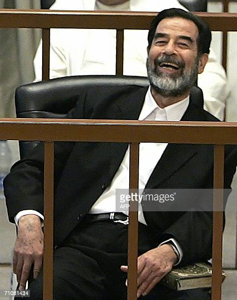 Former Iraqi president Saddam Hussein flashes a smile while listening to defence witness testimony during his trial in the fortified Green Zone in...