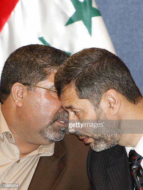 Head of alSadr parliamentary bloc Nassar AlRubaie speaks with an unidentified member of AlSadr bloc during a press conference in Baghdad 16 April...