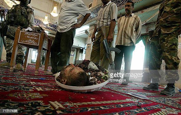 Iraqi army and police look at the head of a a suicide bomber who blew himself up inside Baratha Shiite mosque in Baghdad 16 June 2006 after a suicide...