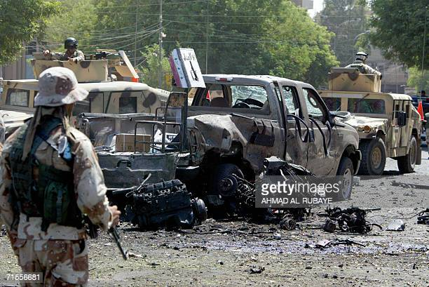 Iraqi army soldiers secure the site where a suicide car bomb ripped through the middle class Baghdad neighborhood of Karrada killing 10 soldiers and...