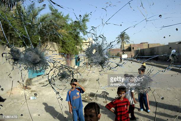 Iraqi boys are seen through the bulletriddled windshield of a car 07 August 2006 at the site where Iraqi and US forces fought overnight a deadly gun...