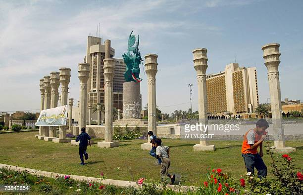 Iraqi children play at Baghdad's alFirdos Square next to the freedom sculpture which replaced the statue of executed leader Saddam Hussein toppled...