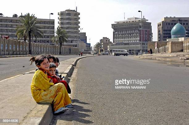 Iraqi children sit in an empty street in central Baghdad 26 February 2006 Security forces kept a tight grip on Baghdad as authorities banned vehicle...