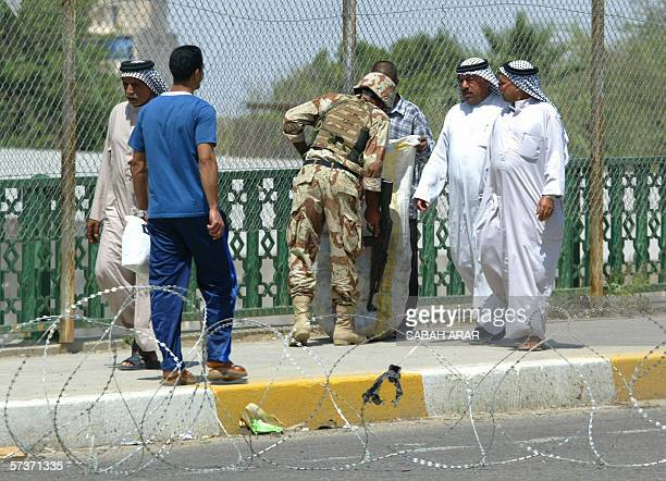 Iraqi men have their bags searched at an Iraqi Army snap checkpoint set up in Baghdad as security services tightened their grip on the capital ahead...