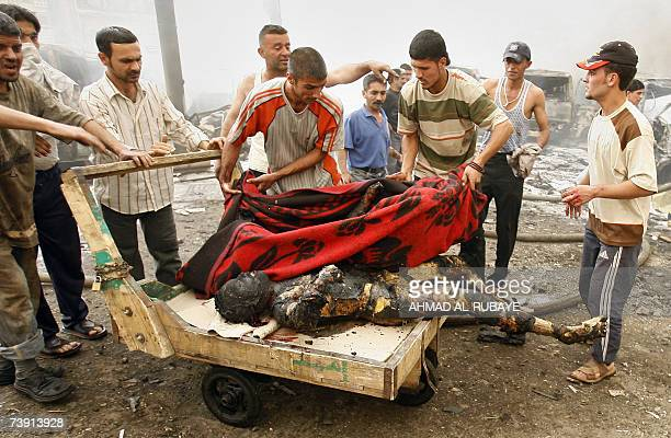 Iraqi men rush to evacuate burned bodies from the site of a car bomb explosion in Baghdad's alSadriyah neighborhood 18 April 2007 in which over a...