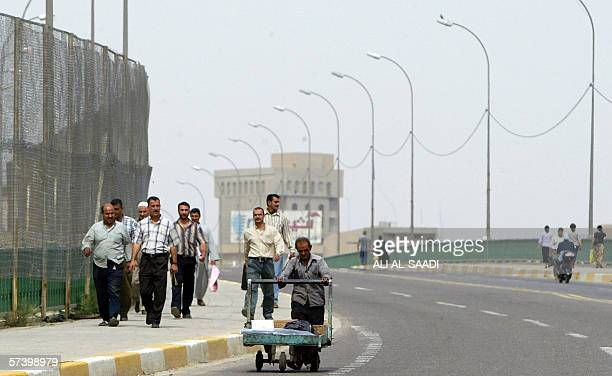 Iraqi men walk across a bridge in central Baghdad following a ban on traffic around the heavily fortified Green Zone where Iraq's parliament session...
