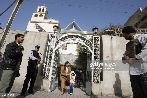 Iraqi police stand guard as worshippers leave Christmas morning mass at the Catholic church in the central Baghdad Karrada neighbourhood 25 December...