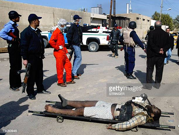 Iraqi policemen gather around the body of an alleged militant outside the morgue of Baghdad's alYarmuk hospital 20 January 2007 US Defense Secretary...