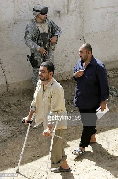 Iraqi prisoners walk past the US soldiers inside the Abu Ghraib prison compound shortly before they are released as another batch of 200 prisoners...