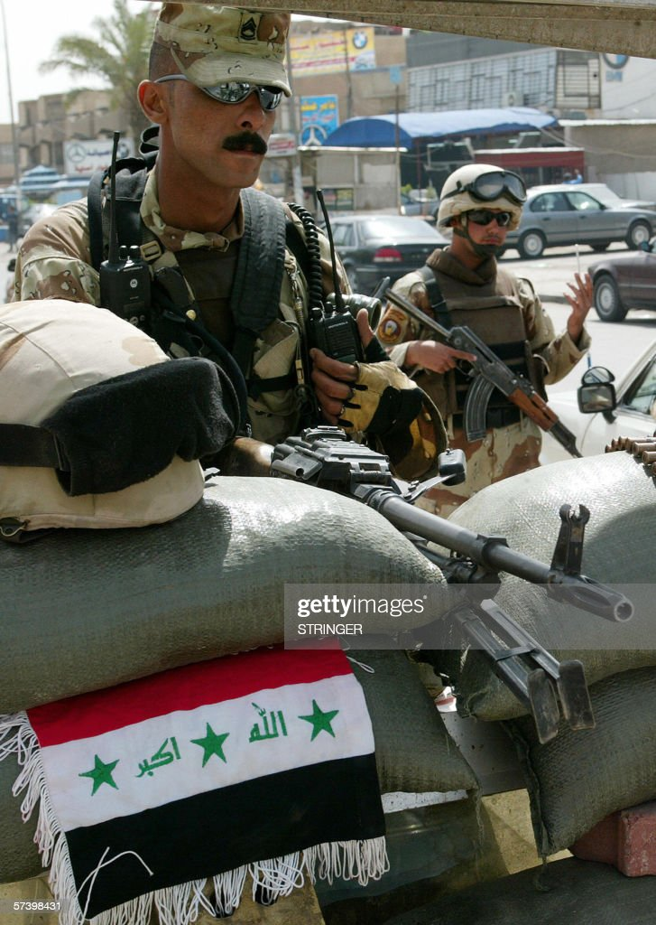 Iraqi soldiers stand guard at a checkpoi : News Photo