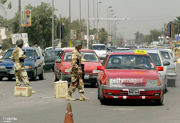 Iraqi soldiers use cardboard boxes as a roadblock in a street in Baghdad 18 June 2006 A wave of bombings and kidnapping have disrupted a massive...