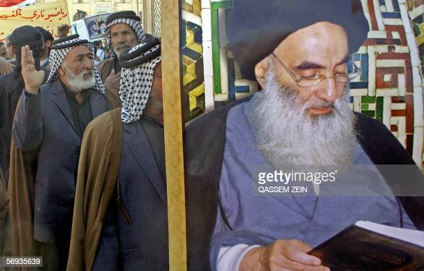 Iraqi tribal men march behind a poster of Grand Ayatollah Ali al-Sistani during a demosntration in the holy city of Najaf, south of Baghdad, 26...