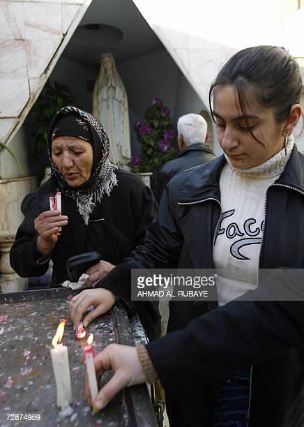 Iraqi women light candles during Christmas morning mass at the Catholic church in the central Baghdad Karrada neighbourhood 25 December 2006...