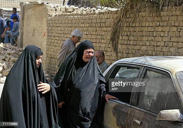 Iraqi women react as they look at the wreckage of car 11 June 2006 the site where a car bomb exploded yesterday in central Baghdad Three Iraqis were...