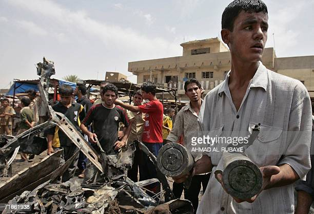 Iraqis carry two shell casings extracted from the wreckage of a car which exploded in Baghdad's poor neighborhood of Sadr City 17 August 2006 Four...