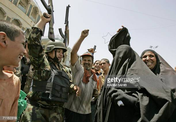 Iraqis dance with soldiers in Baghdad after hearing Iraqi Prime Minister Nuri alMaliki announcing 08 June 2006 the death of alQaeda leader in Iraq...