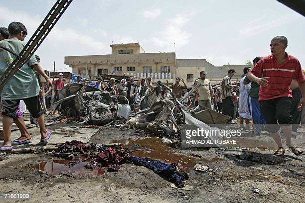 Iraqis gather around the wreckage of a car which exploded in Baghdad's poor neighborhood of Sadr City 17 August 2006 Four Iraqis were killed and 26...