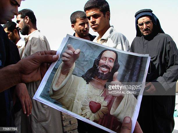 Iraqis inspect a picture of a smiling Jesus at Baghdad's poor neighborhood of Sadr city at the site where residents said was targeted by an overnight...