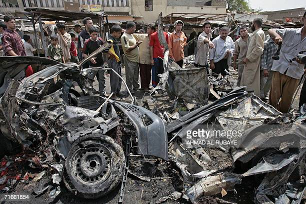 Iraqis inspect the wreckage of a car which exploded in Baghdad's poor neighborhood of Sadr City 17 August 2006 Four Iraqis were killed and 26 others...