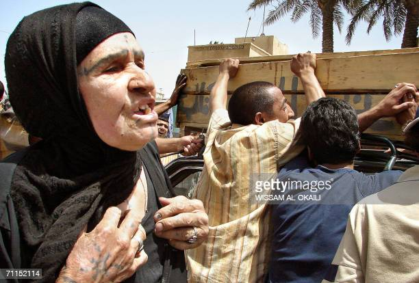 Iraqis mourn over a coffin of a relative outside a local hospital in Baghdad 08 June 2006 Eight Iraqi were killed and 36 were wounded in two separate...