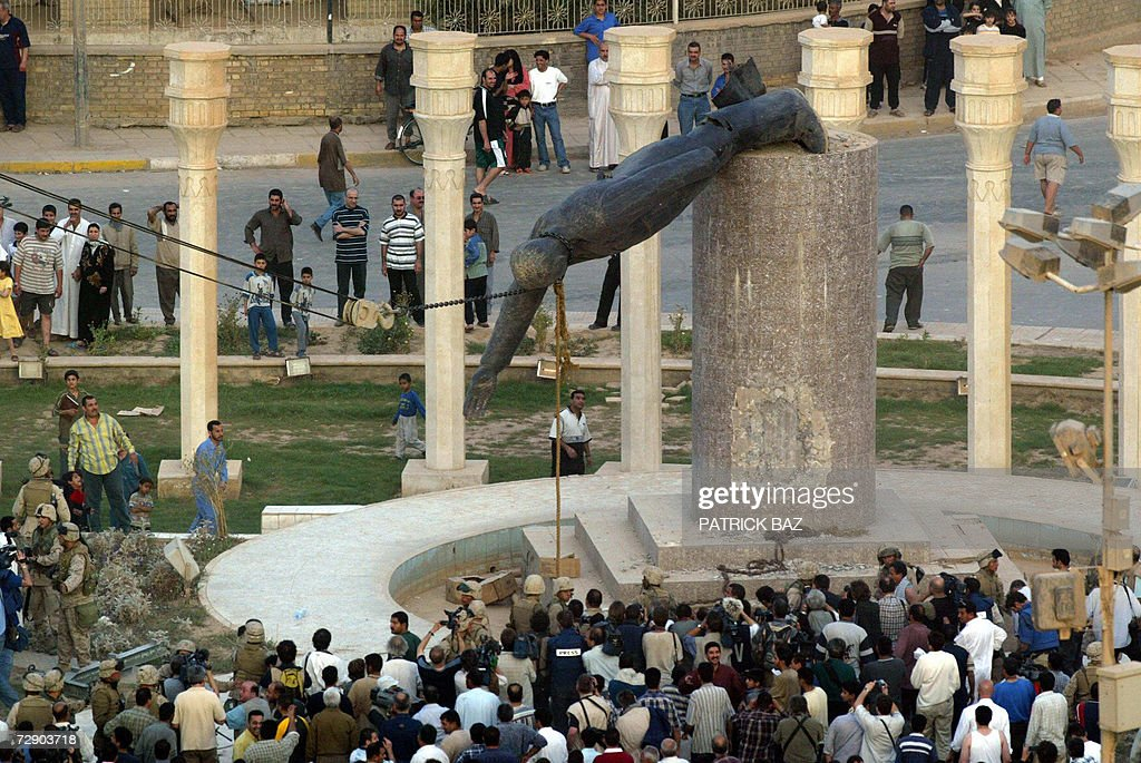 Iraqis watch a statue of Iraqi President Saddam Hussein falling in Baghdad's al-Fardous (paradise) square 09 April 2003. Ousted dictator Saddam Hussein was hanged 30 December 2006 for crimes against humanity, officials said, as Iraq braced itself nervously for possible reprisals by his remaining supporters. AFP PHOTO/Patrick BAZ