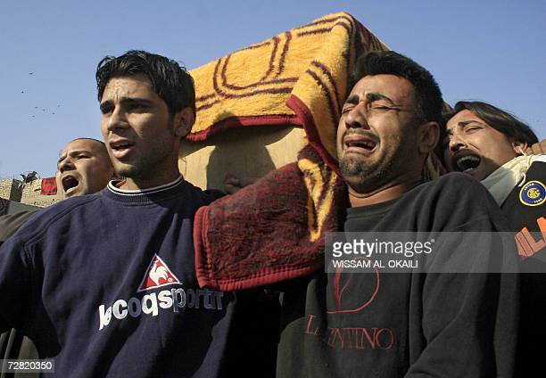 Iraqis weep as they carry the coffin of a relative during his funeral procession in Baghdad's impoverished neighborhood of Sadr City 14 December 2006...