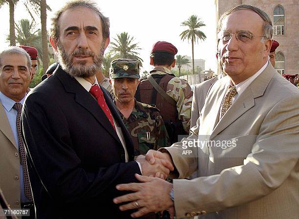 Iraq's new Defence Minister General Abdel Qader Jassem alObeidi greets former defence minister Saadun alDulaimi during a handover ceremony at Iraqi...