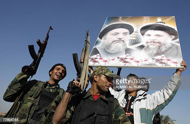 Shiite Iraqi Badr forces hold up a picture of Mohammed Baqr Al-Sadr , assassinated during the regime of ousted President Saddam Hussein in the...