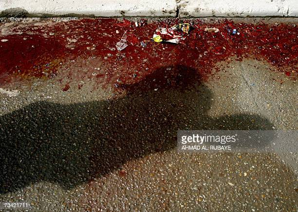 The shadow of an Iraqi bystander is cast on the ground as he inspects a pool of blood at the site where a mortar shell targeted alNidal street...