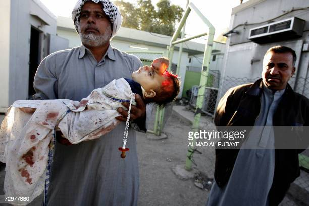 TO GO WITH AFP STORY 'IRAQYEAR2006' An Iraqi carries the body of his grandson out of the morgue of a hospital in Baghdad 21 November 2006 The child...