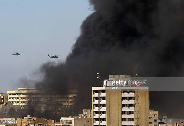 US Blackhawk helicopters patrol the area where thick smoke rises from the site of an explosion in central Baghdad 12 February 2007 A spate of bomb...